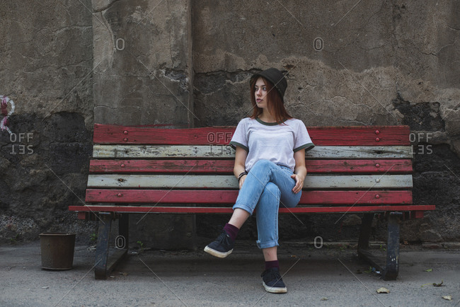 Full body of stylish young woman in informal outfit and hat resting on old bench against aged stone building in city