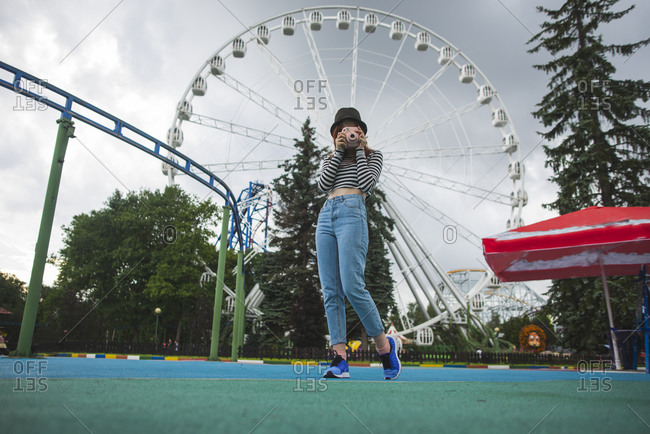 Low angle of young hipster female traveler in trendy outfit and hat covering face with instant camera while capturing pictures in amusement park against Ferris wheel during summer weekend in Saint Petersburg