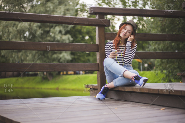 Full body of carefree young red haired female student in stylish casual outfit and hat holding smartphone and adjusting earphones while listening to music and chilling on wooden bridge in summer park