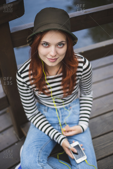 Young red haired female student in stylish casual outfit and hat holding smartphone and listening to music and chilling on wooden bridge in summer park