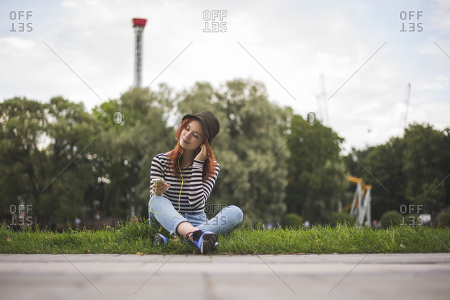 Young red haired female student in stylish casual outfit and hat holding smartphone and listening to music and chilling in summer park