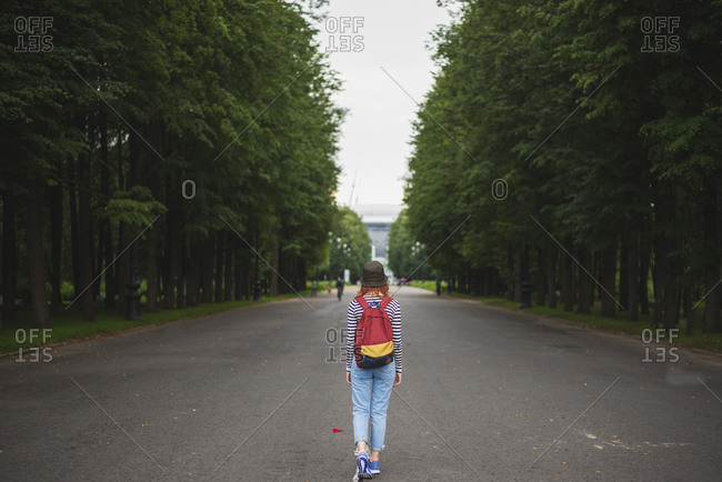 Back view of anonymous hipster female traveler with colorful backpack walking on asphalt alley between green trees in summer park in Saint Petersburg