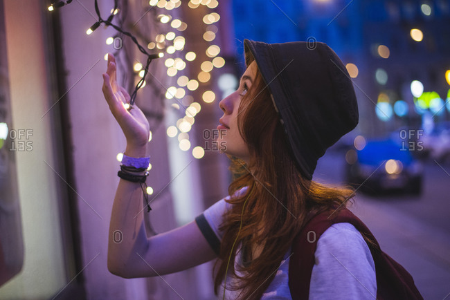 Side view of stylish hipster millennial woman in hat and with backpack touching glowing garland while standing near building in evening city