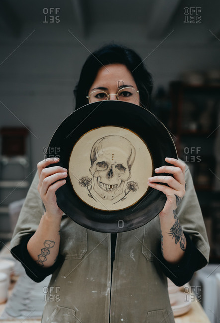 Creative female artisan in dirty clothes covering face with handmade clay plate with drawn skull and looking at camera