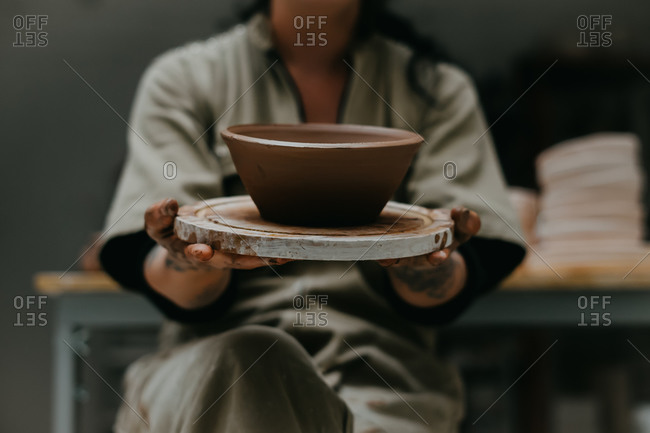 Unrecognizable crop female ceramist with dirty hands showing handmade pot while sitting in art workshop