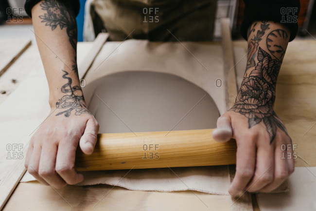 High angle of crop anonymous craftsman shaping piece of clay with wooden rolling pin while creating handicraft earthenware in art workshop