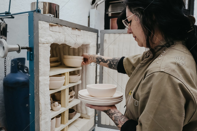 Unrecognizable crop artisan putting clay bowls and pots on shelf in creative studio