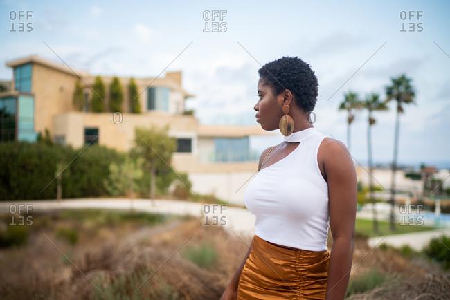 Trendy pondering African American female in earrings admiring ocean under cloudy sky while looking away