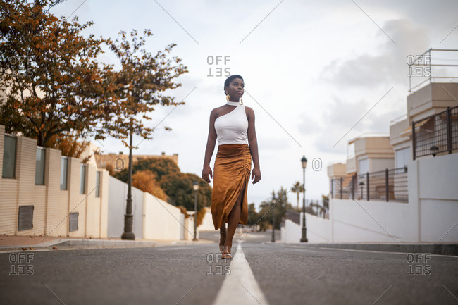 Ground level of young dreamy African American female in trendy apparel strolling on asphalt roadway while looking away