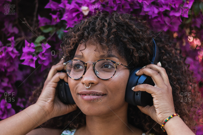 African American female with piercing and glasses smiling and listening to music in headphones against blooming bush