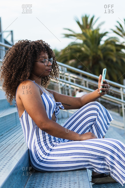 Positive African American female in striped apparel and taking selfie while sitting on stairs on city street