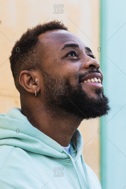 Happy adult African American hipster male laughing while standing against yellow wall on street