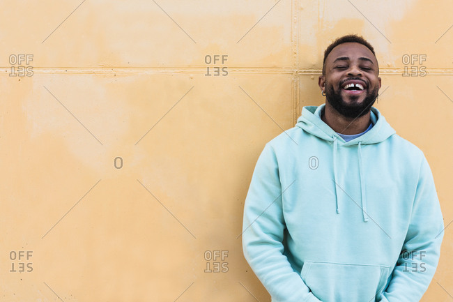 Happy adult African American hipster male with missing tooth wearing blue hoodie laughing while standing against yellow wall on street