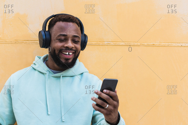 Positive adult bearded African American male in hoodie listening to music with wireless headphones and browsing smartphone while standing against yellow wall