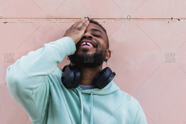 Cheerful adult African American bearded guy in casual wear with headphones on neck covering eye against gray wall