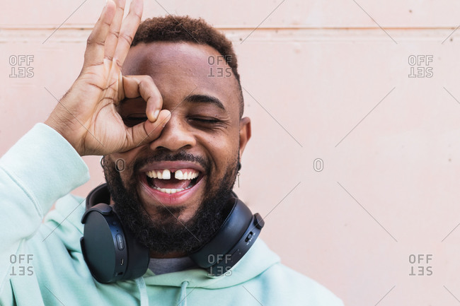 Cheerful adult African American bearded guy in casual wear with headphones on neck looking through  fingers showing okay sign against gray wall