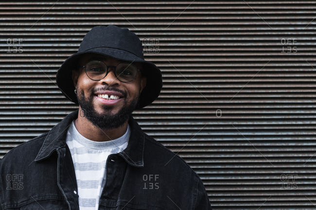 Happy African American bearded guy in eyeglasses wearing trendy casual outfit and hat smiling brightly and looking at camera while standing against shuttered wall
