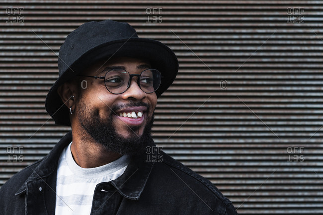 Happy African American bearded guy in eyeglasses wearing trendy casual outfit and hat smiling brightly and looking away while standing against shuttered wall