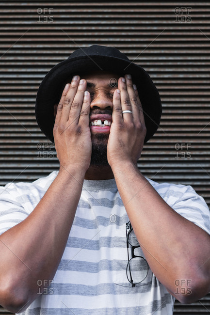 Positive adult African American male in casual striped shirt and trendy hat covering eyes with hands while standing against grunge wall on street