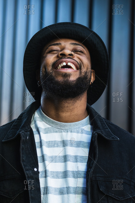 Happy African American bearded guy wearing trendy casual outfit and hat smiling brightly and looking up while standing against shuttered wall