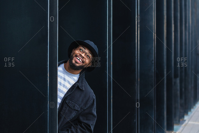 Optimistic adult black hipster male in hat and glasses peeking out of pillar of modern urban building and looking away with curiosity