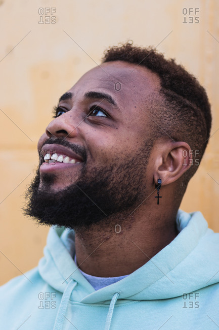 Happy adult African American hipster male wearing blue hoodie laughing while standing against yellow wall on street