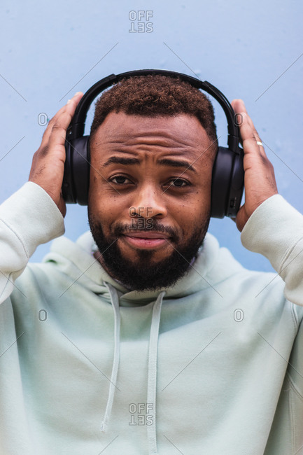 Happy adult bearded African American male in blue hoodie enjoying music with wireless headphones against blue background