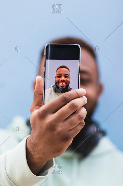 Cheerful adult black hipster guy in casual outfit with headphones on neck taking self portrait on mobile phone against blue background