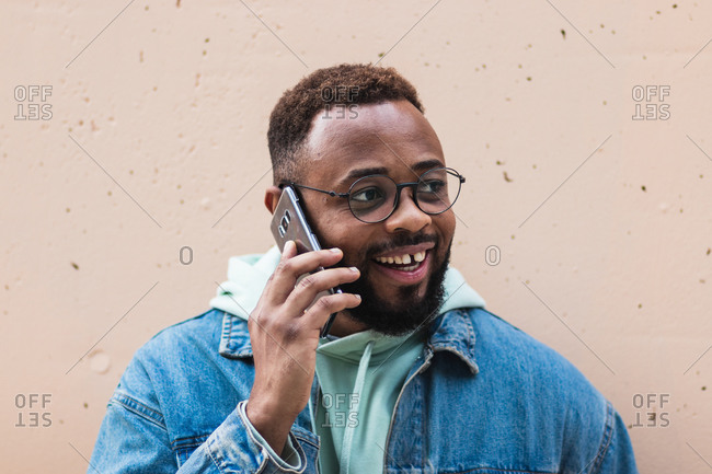 Adult hipster bearded African American male in casual outfit and glasses having phone conversation and laughing satisfied with news while standing against beige stone wall on street