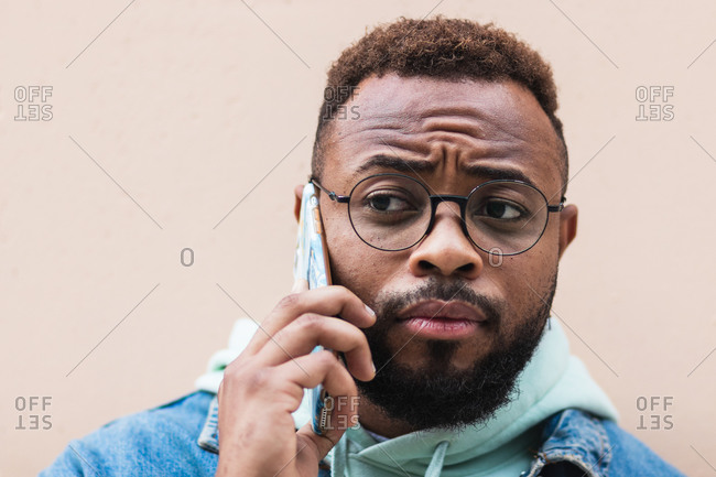Adult hipster bearded African American male in casual outfit and glasses having phone conversation while standing against beige stone wall on street