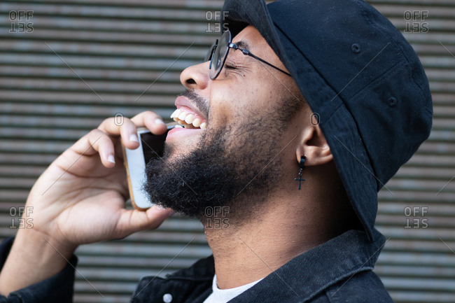Side view of excited laughing black bearded male in trendy hat and glasses enjoying phone conversation while standing against gray wall on street