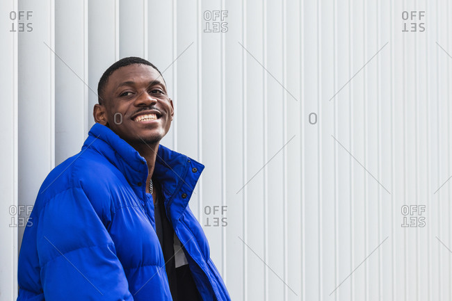 Side view of cheerful African American male model wearing vivid blue jacket while standing on metal wall on the street and looking away