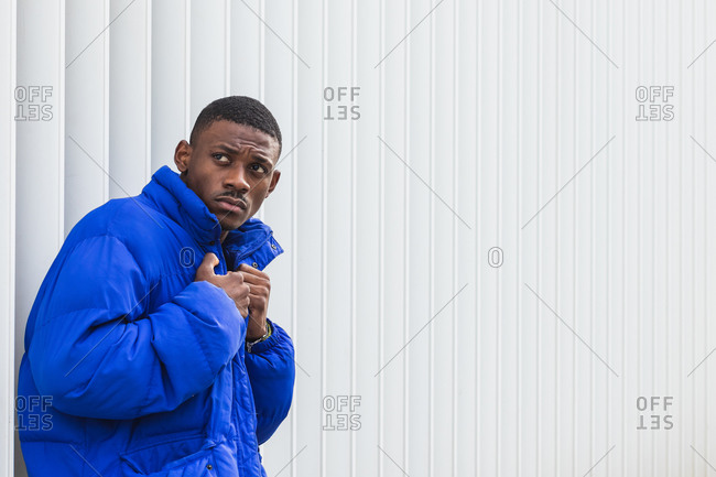 Side view of confident African American male model wearing vivid blue jacket while standing on metal wall on the street and looking away
