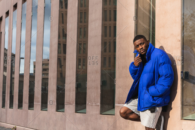 Confident African American male model wearing vivid blue jacket while standing on modern building on the street and looking away