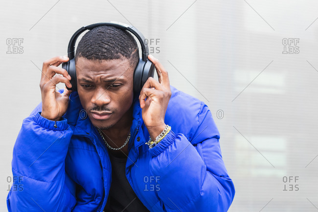 Calm ethnic male wearing stylish hipster outfit sitting on stone border on street in headphones and enjoying songs while looking away