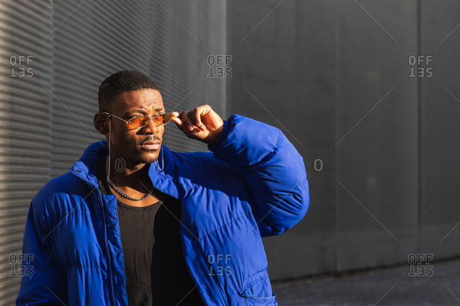 Confident African American male wearing trendy orange sunglasses and warm jacket standing near metal wall of modern building in city and looking away