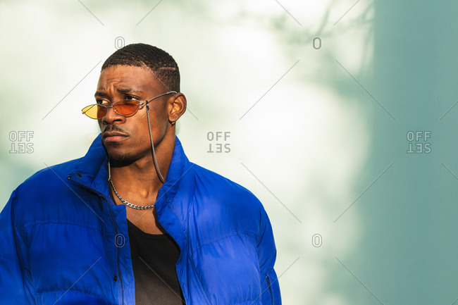Confident African American male wearing trendy orange sunglasses and warm jacket leaning on wall in the city and looking away