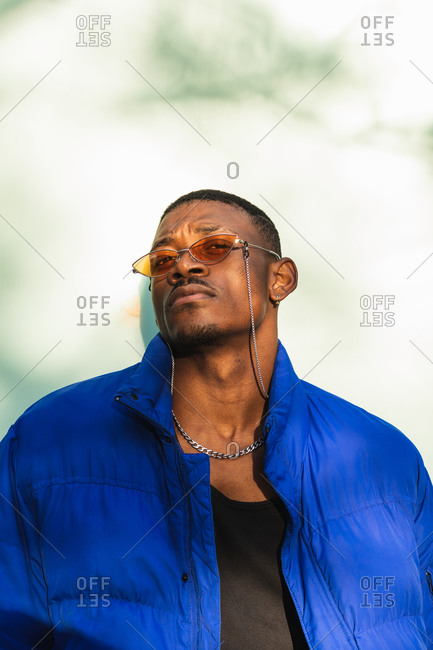Confident African American male wearing trendy orange sunglasses and warm jacket leaning on wall in the city and looking at camera