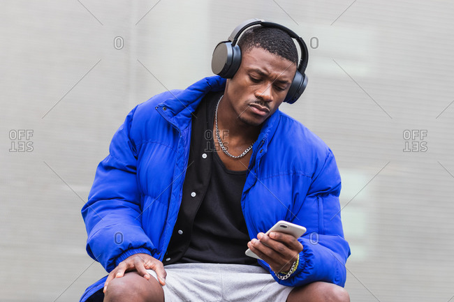 Calm ethnic male wearing stylish hipster outfit sitting on stone border on street in headphones and using mobile phone while looking away