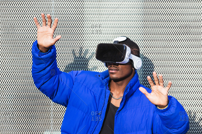 African American male standing on street near metal fence while exploring virtual reality in innovative goggles and touching air