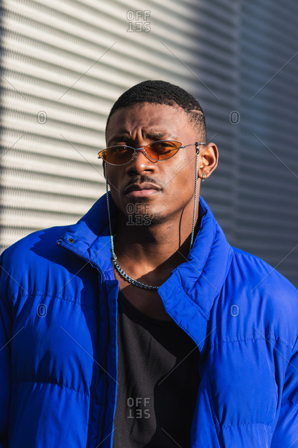 Confident African American male wearing trendy orange sunglasses and warm jacket standing near metal wall of modern building in city and looking at camera