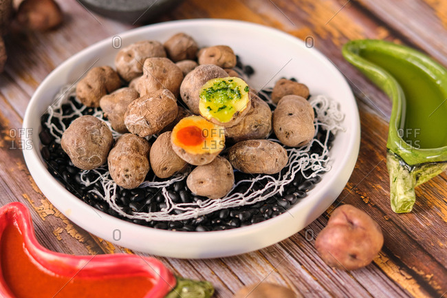 From above of tasty potatoes with wrinkly peel in plate on black beans on wooden table