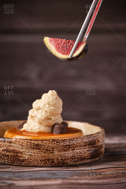 Faceless chef adding piece of ripe fig on top of sweet cheesecake with whipped cream served on table in cafe