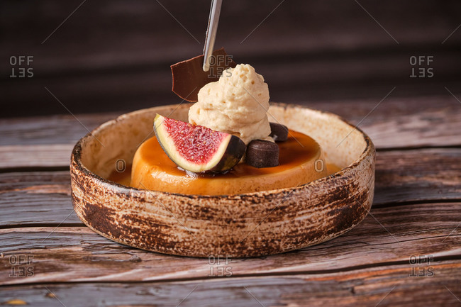 Faceless chef adding piece of delicious chocolate on top of sweet cheesecake with whipped cream and ripe figs served on table in cafe