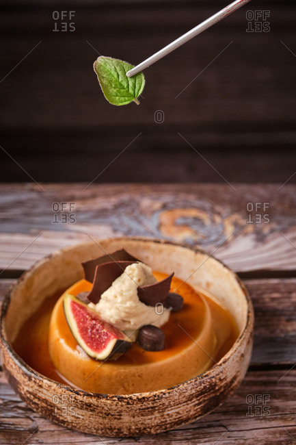 Cropped anonymous male chef adding leaf of mint on tasty cheesecake with whipped cream and piece of fig served on wooden table