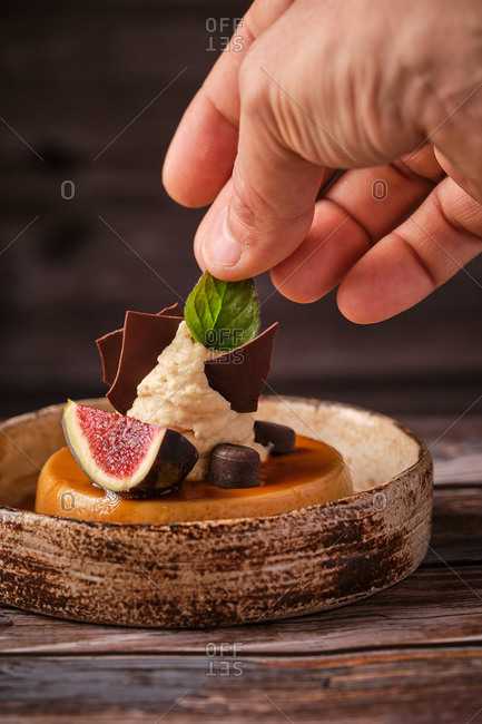 Closeup of anonymous crop male chef adding leaf of mint on tasty cheesecake with whipped cream and piece of fig served on wooden table