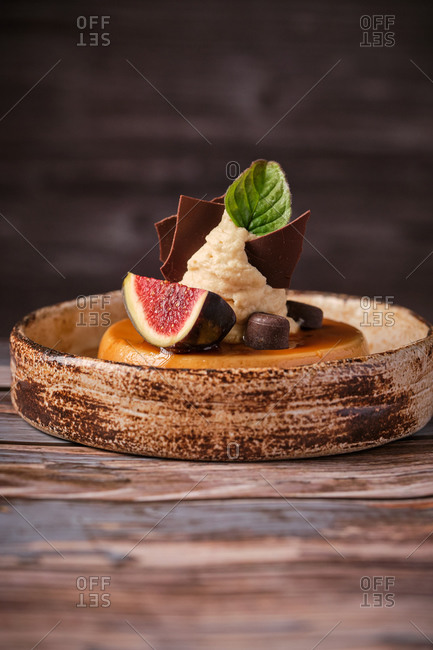 Tasty caramel cheesecake with fig and green basil in plate with spoon on wooden table in cafe