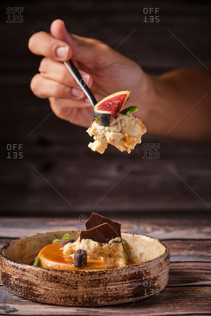 Cropped unrecognizable person with spoon of tasty caramel cheesecake with shipped cream and piece of fig at wooden table in cafe