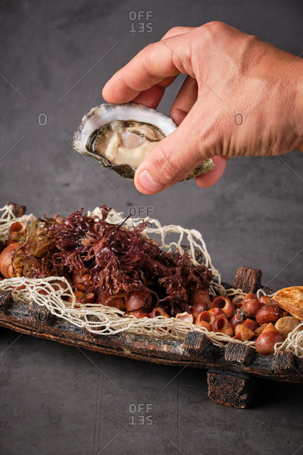 Cropped unrecognizable person hands holding palatable oyster in shell served in plate with various seafood ingredients in Asian restaurant