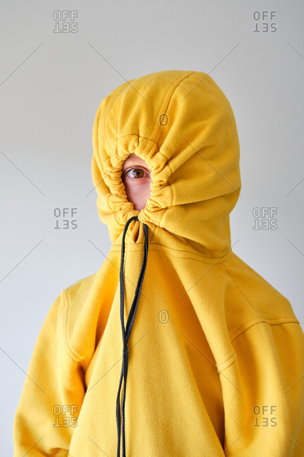 Anonymous expressive teenager hiding in yellow hoodie and looking at camera on gray background in studio
